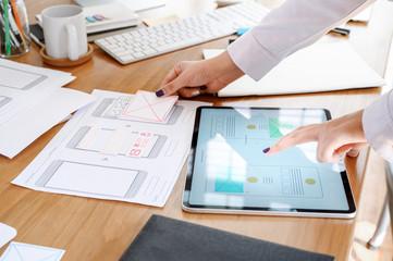 UX designer team using tablet designing smartphone prototype or application layout at office desk.