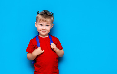 Happy smiling boy in red t-shirt with glasses on his head is going to school for the first time. Child with school bag. Kid on blue background background. Back to school