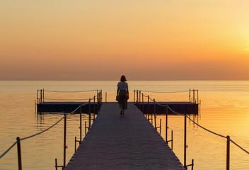 girl on pontoon pier at sunset