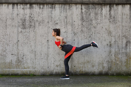 Urban fitness outdoor workout. Fit athlete exercising with resistance band to strengthen the glutes.