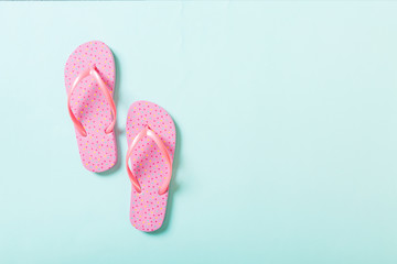 pink flip flops on blue background. Top view with copy space