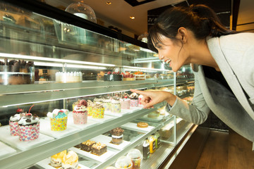 Many Good Looking design and colorful Bakery Cake in refrigerator windows show, present variety of Price and vanilla chocolate birthday cake for special occasion, selected by skinny asian woman dress Fototapete