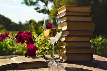 Sweet time with books, wine and flowers in the background.