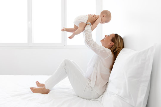 Mother sitting on bed lifting her baby in the air