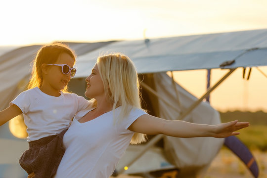 happy family at sunset. mother and her child daughter looking at the flying plane in the sky