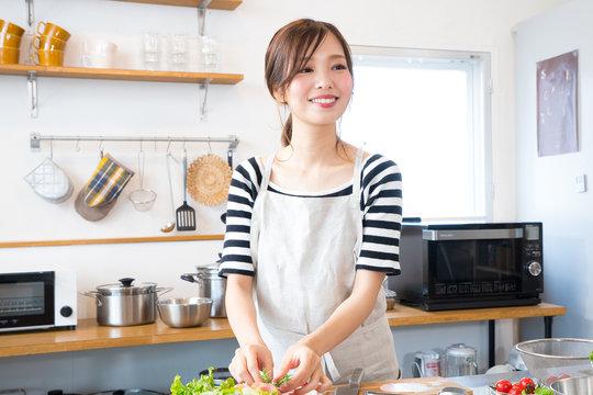 キッチンで料理を作る若い主婦