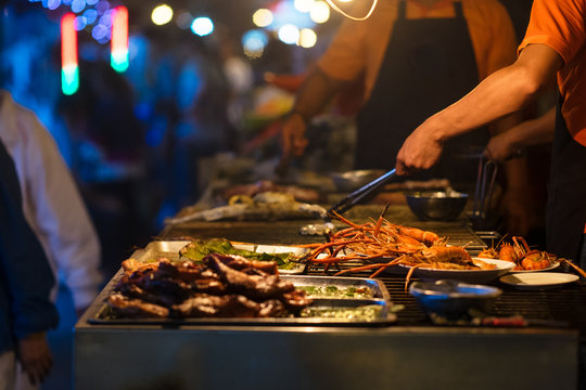 Chef cook the bbq seafood in near beach for dinner part, roasted seafood party,grilled lobster cook on charcoal stove. Grilled king prawns and squid on bbq fire. Thai street food