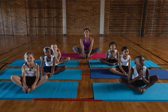 Female yoga teacher and schoolkids doing yoga and meditating on a yoga mat in school