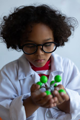 Schoolboy examining molecule model in laboratory