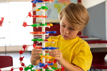 Boy studying science model in classroom