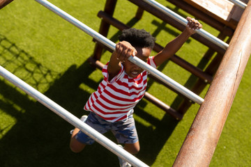 Schoolboy playing on horizontal ladder in the school playground