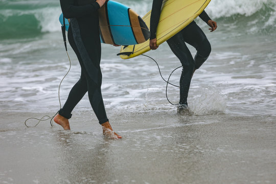 Male friends walking on beach while holding surfboard