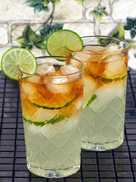 Dark'n Stormy Cocktails made with dark rum and ginger beer, decorated with lime slices