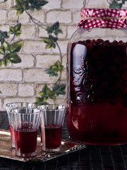 Sour cherry liqueur in crystal glasses and a large jar of homemade sour cherry liqueur