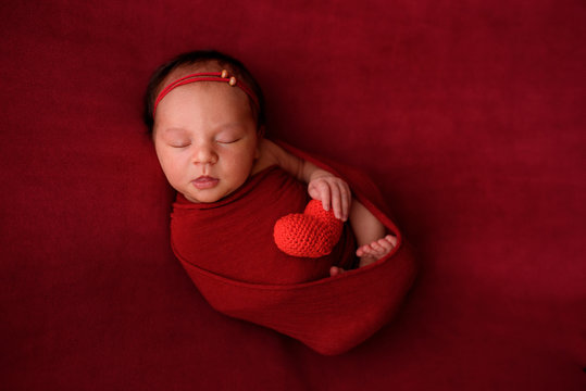 Newborn girl sleeping on a red cloth in a red wrapper