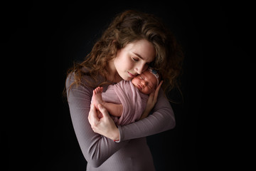 Mom is holding her newborn daughter. Picture taken on a dark background.