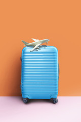 Suitcase and airplane model, minimal creative travel concept.