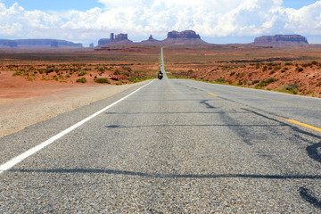 Fototapete - motorcycle approaching on straight road in Monument Valley