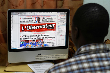The graphic designer for the Observateur Paalga newspaper shows the front page with headlines on the new laws restricting reporting on security issues in Burkina Faso, in Ouagadougou