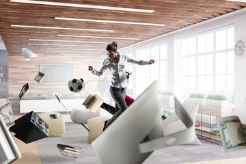 Business woman playing footbal in office