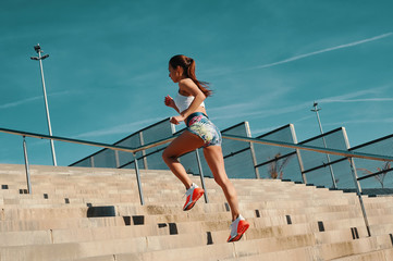 Training to become the best. Full length of beautiful young woman in sports clothing running while exercising outdoors