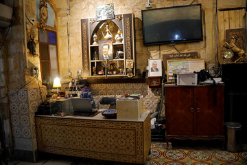 Picture of Syria's President Bashar al-Assad is seen above a desk in a coffee shop in Jenin, in the Israeli-occupied West Bank