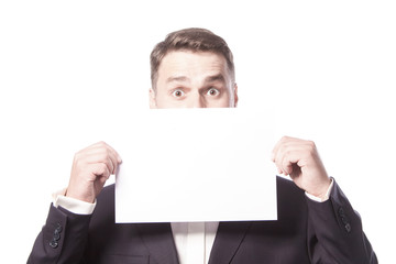 A man closes his mouth with a white sheet, a surprised look.