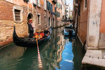 Venetian gondolier punts gondola through narrow canal waters of Venice, Italy