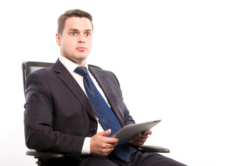 Surprised man in a suit with a tablet in his hands sitting in a chair on a white background in the studio.