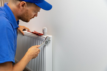 house heating system installation plumber installing radiator