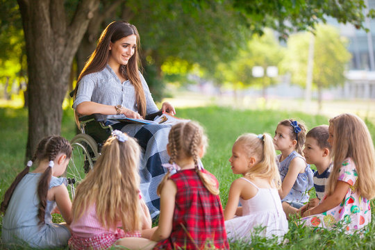 children hold a lesson with the teacher in the park on a green lawn.