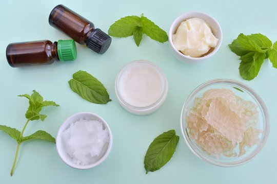 Homemade cosmetic, lip balm with natural ingredients, bee wax, coconut oil, shea butter and essential oils, top view, recipe.