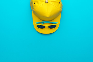Top view photo of yellow baseball cap and sunglasses as summer concept. Flat lay image of summertime accessories over blue turquoise background with copy space and upside position.