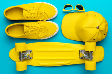 Top view of yellow modern teenage accessories in oder. Flat lay image of yellow baseball cap, sunglasses, sneakers, mini cruiser skateboard over blue turquoise background