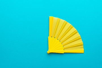 Top view of yellow hand fan over blue turquoise background with copy space. Minimalist flat lay photo of vivid opened fan.