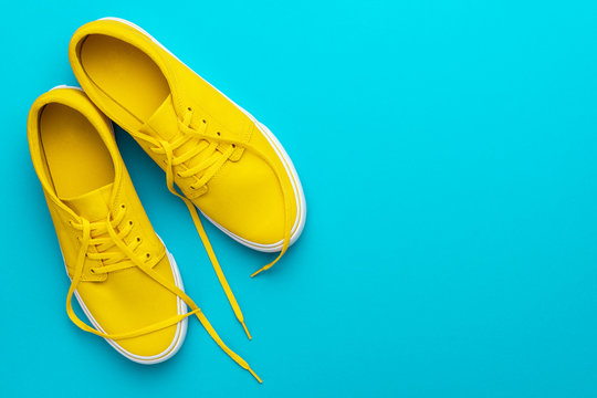 Top view photo of pair of yellow untied sneakers. Minamalist flat lay image of yellow summer footwear over blue turquoise background with copy space. Left side composition of vivid gumshoes.