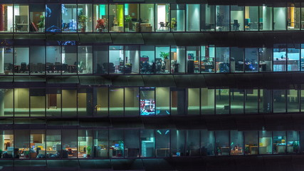 Working evening in glass office building with numerous offices with glass walls and windows timelapse Fotobehang