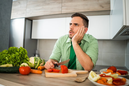 Young man does not know what to prepare for meal.