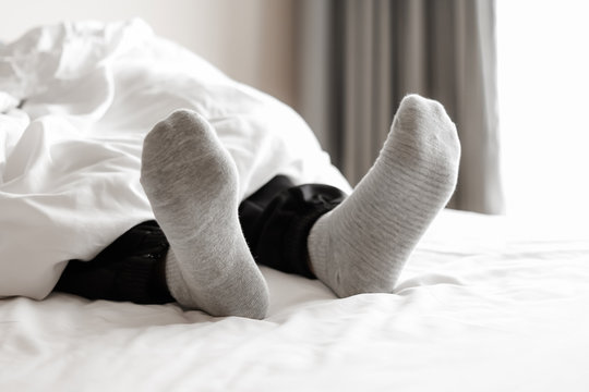 gray socks relaxing on the white bed