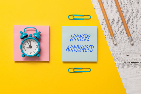 Conceptual hand writing showing Winners Announced. Concept meaning Announcing who won the contest or any competition Notepads colored paper sheet markers alarm clock wooden background