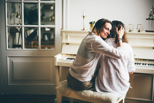 Girlfriend spend time together in modern apartment. Back view two girls learning piano playing on small instrument in white bright room and enjoying togetherness. Concept LGBT couple at home.