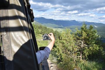Photo-safari trip in Rodopa Mountain, Bulgaria. Male hand holding a digital photo camera from the SUV window