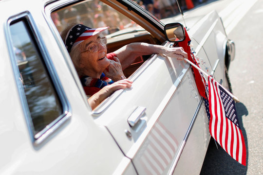 Mabel Wittenmeyer waves a U.S. flag as she rides in a car during the annual 4th of July parade in Barnstable Village on Cape Cod, Massachusetts