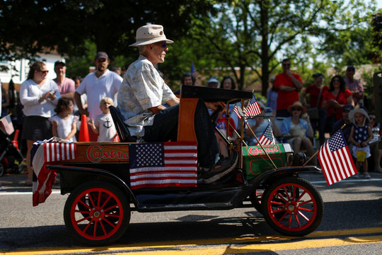 A man rides in a miniature a car during the annual 4th of July parade in Barnstable Village on Cape Cod, Massachusetts
