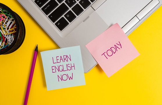 Text sign showing Learn English Now. Business photo text gain or acquire knowledge and skill of english language Trendy metallic laptop sticky notes clips container pencil colored background
