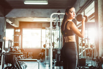 Young girl playing dumbbell to exercise in fitness.Slim girl lifts heavy dumbbell while training in the gym. Sports concept fat burning and a healthy lifestyle. Fototapete