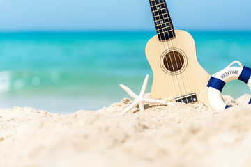 The Summer day with Guitar ukulele items travel for relax and chills on the beautiful beach and blue sky background,copy space. Travel and Summer Concept