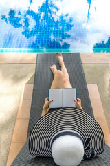 Summer time and Vacations. Women lifestyle relaxing and reading book in luxury swimming pool sunbath, summer day at the beach resort in the hotel. Summer Concept.
