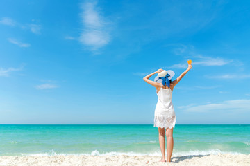 Summer Day. Lifestyle  woman wearing white dress fashion summer beach  on the sandy ocean beach. Happy woman enjoy and relax vacation and holiday. Travel Concept.