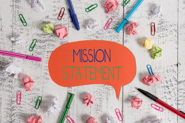 Handwriting text Mission Statement. Conceptual photo Formal summary of the aims and values of a company Blank speech bubble pens clips crushed paper balls vintage retro table